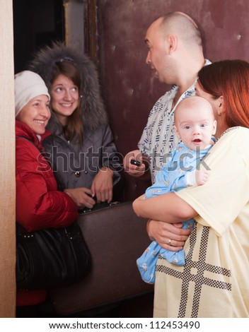 Family of three is meeting a kinsfolk at home. Focus on baby only