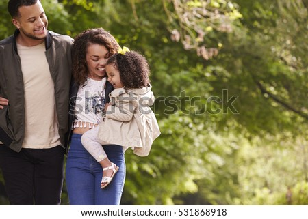 Family of three on a walk, mother holding child, close up