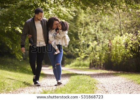 Family of three on a walk, mother holding child, front view