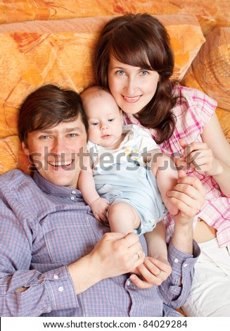 Family of three people lying down at bed, cuddling and smiling. High angle view