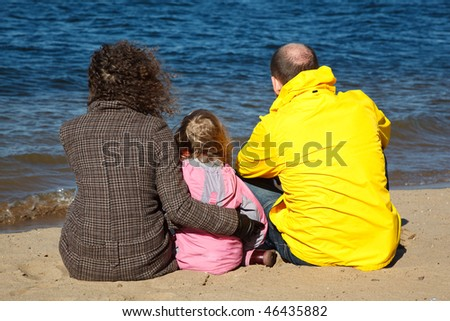 Family of three people sitting on sand on river bank. View from back.