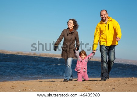 Family of three people walking along beach. Sunny autumn day.