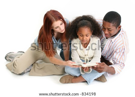 Family of three reading child's bible together.  Caucasian mother and African American Father with daughter.