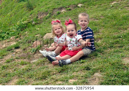 Family of three sit outdoors on grassy hillside.  Small boy attempts to hold his smallest sister, while other sits quietly besides him.