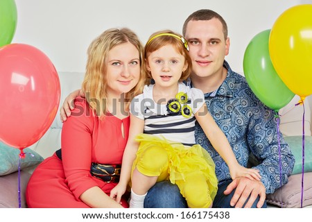 Family of three sits on sofa in light room decorated with birthday air balloons, daughter sits on father knee
