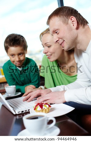 Family of three spending time at a cafe surfing internet
