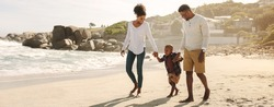Family of three taking a walk along the sea shore. Man and woman holding hands with their son and walking on beach.