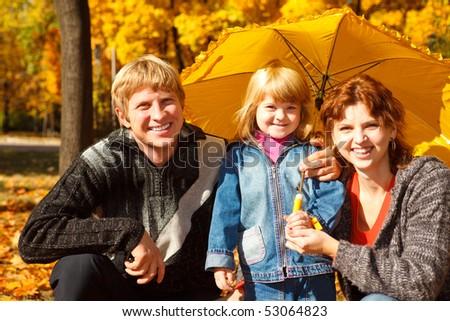 Family of three under umbrella in the autumn park