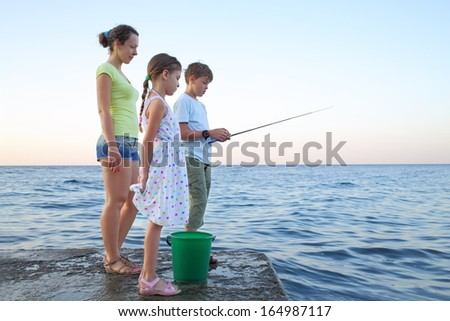 Family of three with a fishing rod fishing in the sea