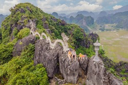 Family of tourists on the background of Amazing huge dragon statue at limestone mountain top near Hang Mua view point at foggy morning. Popular tourist attraction at Tam Coc, Ninh Binh. Vietnam travel