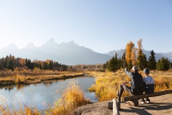 family of two, father and son, hiking and enjoying the gorgeous views in grand teton national parl, wyoming, during fall, active family vacation concept