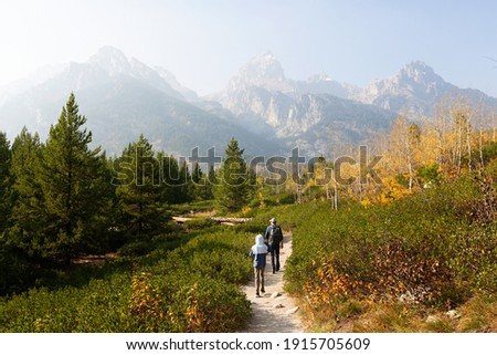 family of two, father and son, hiking and enjoying the gorgeous views in grand teton national parl, wyoming, during fall, active family vacation concept Foto stock ©
