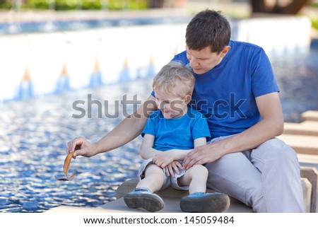 family of two floating a leaf boat