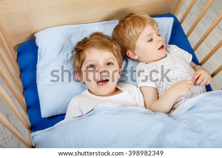 Family Of Two Little Brothers Boys Having Fun In Bed At Home Indoors