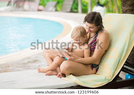 Family of two resting by the pool interested in what is shown on the tablet screen