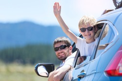 family of two smiling and looking out of the car enjoying road trip in california, vacation concept
