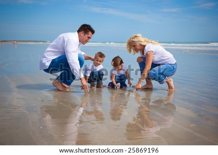 Family on a beach looking at findings in the sand