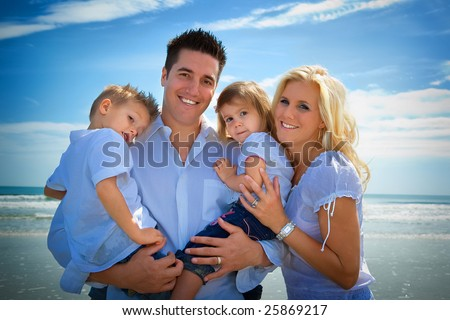 Family on a beach, standing, looking into camera. - stock photo