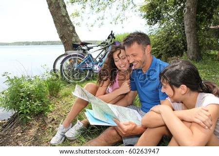 Family on a bicycle ride looking at map