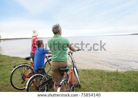 Family on a bike ride standing by a lake
