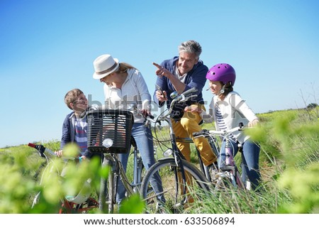Family on a biking day making a stop and using smartphone