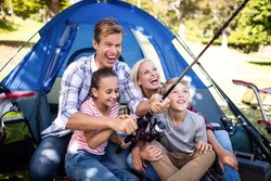 Family on a camping trip fishing outside their tent