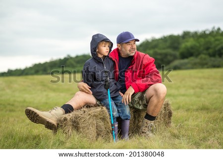 Family on a trekking day. Father and son relaxing after a forest and plain trail, focus on father