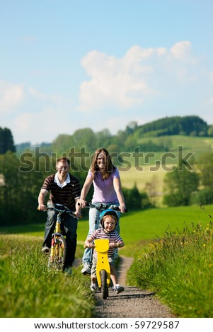 Family on a trip with their bicycles in a wonderful scenery, since their son is so young he is riding a training bike