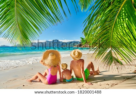 Family on beautiful Anse Soleil beach with palm tree, young couple with three year old toddler boy. Summer vacation at Seychelles, Mahe. Photo stock ©