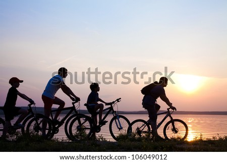 family on bicycles admiring the sunset on the lake. silhouette