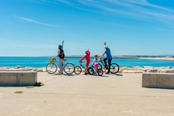 Family on bicycles looking at the beach on sun shining travel vacation day blue sky coastline outdoors background. Horizontal shot. Back view picture of happy exciting people on holiday