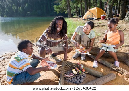 Family on camping trip by lake cooking food on barbecue