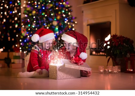 Stock Photo Family on Christmas eve at fireplace. Kids opening Xmas presents. Children under Christmas tree with gift boxes. Decorated living room with traditional fire place. Cozy warm winter evening at home.