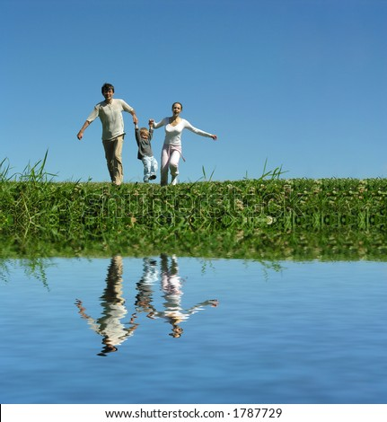 family on herb under blue sky and water