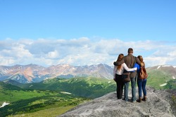 Family on hiking trip in Rocky Mountains National Park, Colorado, USA. Father with arms around his family looking at beautiful summer mountains landscape. People standing on  top of  mountain rock.