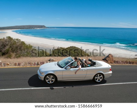 Family on holiday driving convertible on road with beach and ocean in background