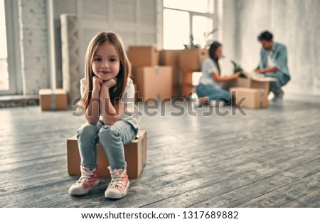 Family on moving day. Attractive young woman and handsome bearded man with their cute little daughter are happy to move into new home.