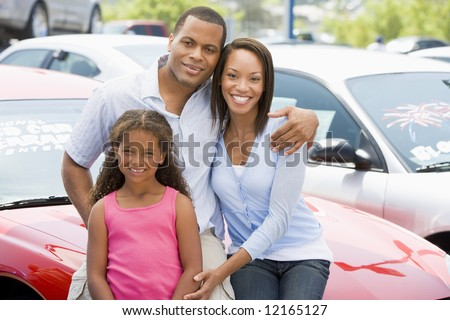 Family on new car lot looking to camera