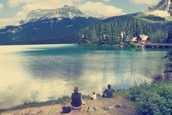 Family on the bank of Emerald lake (Yoho National park. Alberta. Canada) Image done with a vintage retro instagram filter