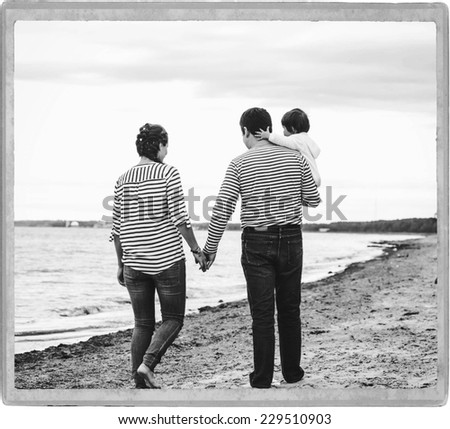 family on the beach father and mother with child in same clothes black and white