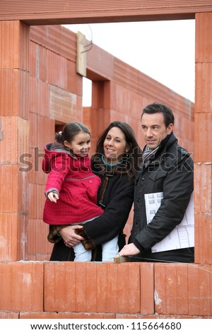 Family on the building site of their new home