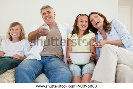 Family on the sofa watching tv together