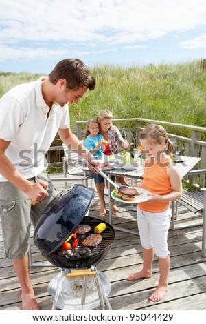 Family on vacation having barbecue - stock photo