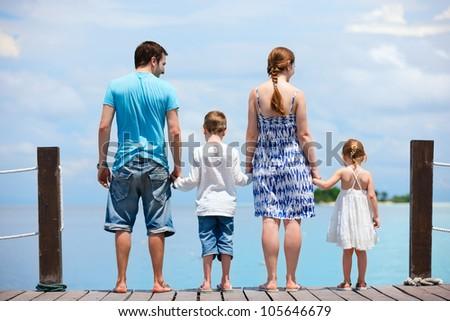 Family on wooden dock enjoying ocean view