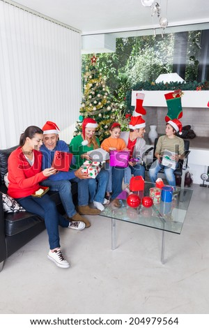 Family open gift box christmas holiday parents, senior grandparents and children give present sitting on sofa living room