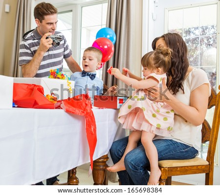 Family opening birthday presents with man taking picture through camera