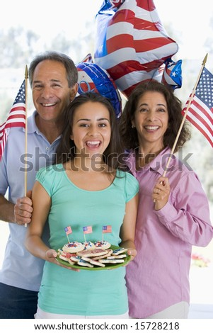 Family outdoors on fourth of July with flags and cookies smiling