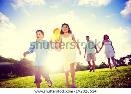 Family outdoors walking toward the camera.