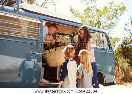 family packing up their camper...