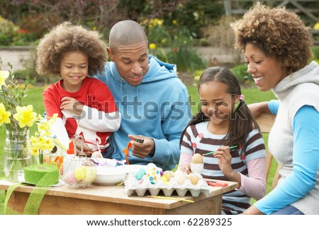 Family Painting Easter Eggs In Gardens - stock photo